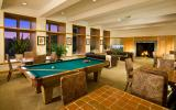 a photo of a lounge area available to residents at Paladin Club Condominiums featuring a pool table, chairs/tables/couches, and a fireplace