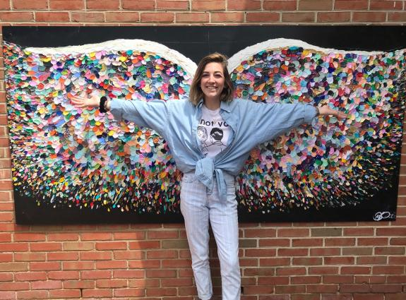 Artist Becca Pettinaro standing in front of colorful wings