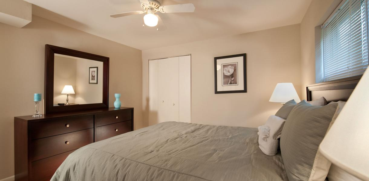a bedroom in Greenville Place Apartments featuring a ceiling fan