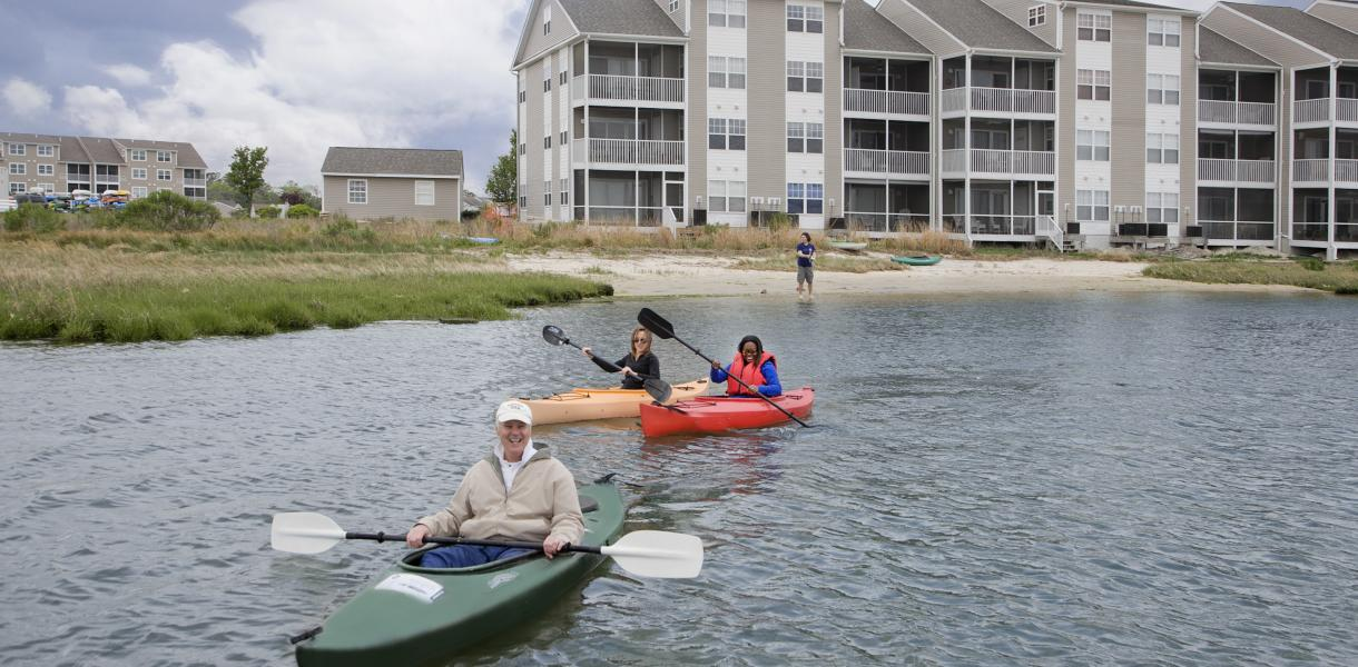 group of kayakers in the water with Bethany Bay Resort Community & Golf Club in the background