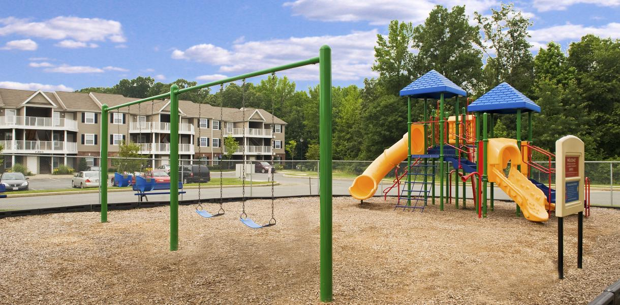 image of a playground for the children of West Creek Village with the apartments in the background