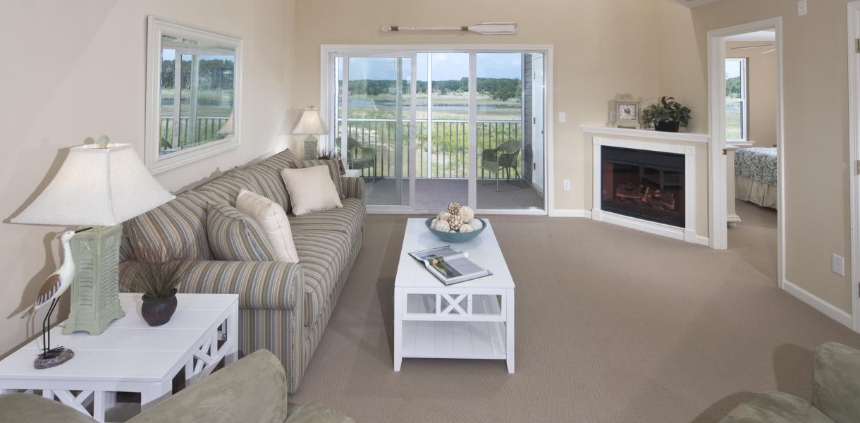 a living room in Bethany Bay Resort Community & Golf Club with a view of the bay in the background